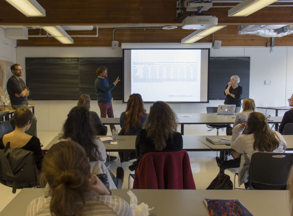 A photo of three professors teaching a class, with students in the foreground.