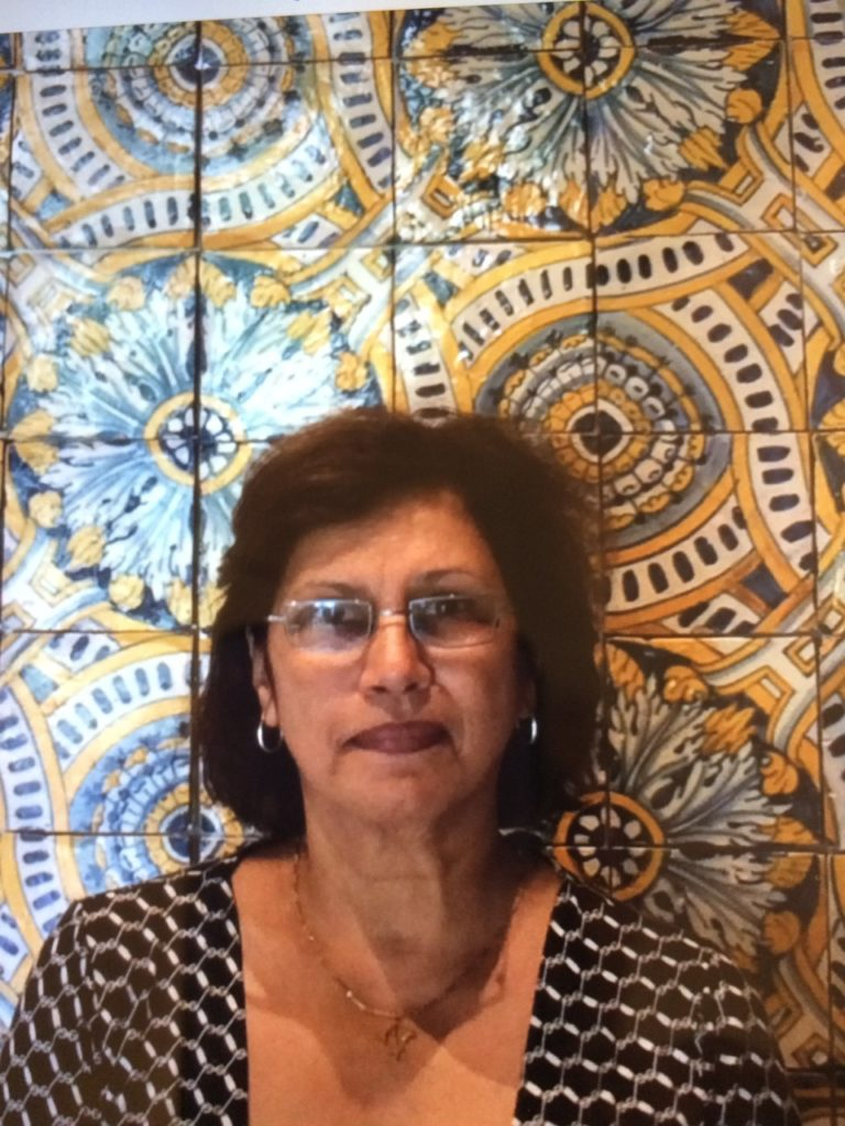 A photograph of Iris Lopez, a woman, in front of a mosaic tile wall, taken in Lisbon, Portugal.