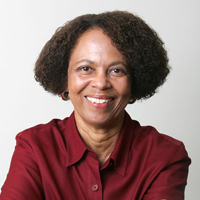 A photograph of Professor Leith Mullings.  She is smiling, wearing a red shirt.